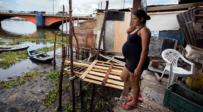 epa05119333 A pregnant woman stands at her house in a zone of the shanty town of Beco do Sururu, located close to Boa Viagem, the richest neighborhood of city of Recife, Brazil, 22 January 2016. Recife is the Brazilian city with more cases of Zika virus. Brazilian government have organized a group of 250,000 people between militarymen and health authorities to try to erradicate the mosquito that transmit the virus.  EPA/Percio Campos
