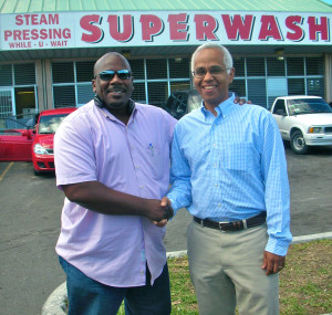 Dionisio D'Aguilar (right) standing infront his Superwash business.